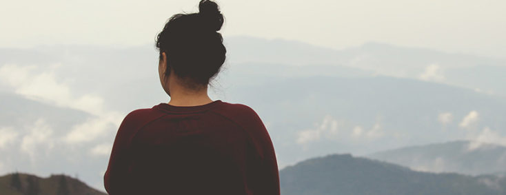 Photograph of a young woman with her back to the viewer looking out over a hilly vista